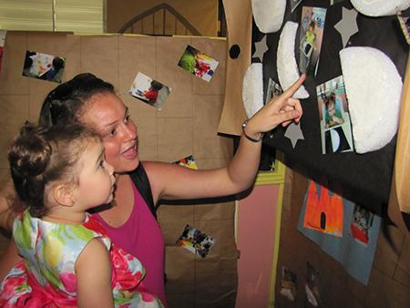 Adulto enseña láminas a niña en brazos