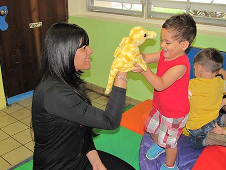 Maestra y niño jugando con marioneta