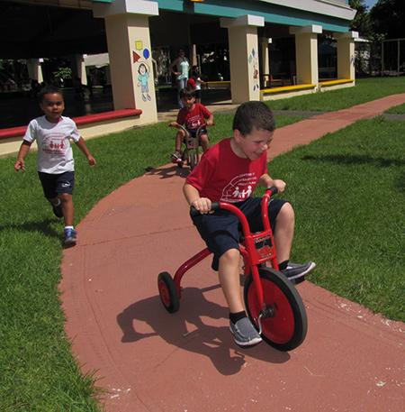 Niño corriendo un triciclo