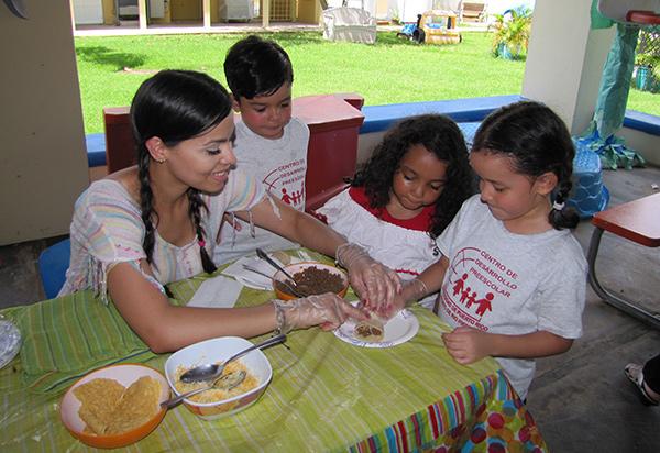 Maestra y niños preparan alimentos