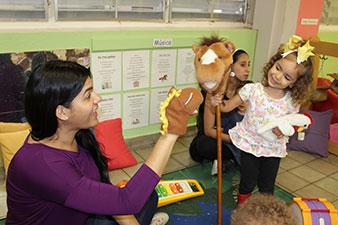 Maestra y niña juegan con marionetas