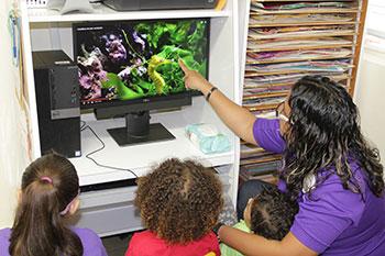 Maestra y niños observan imágenes en una computadora
