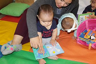 Maestra e infante contemplan un libro con láminas