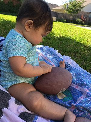 Bebé contempla una bola de fútbol americano.