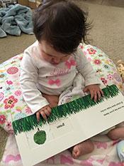 foto 1 de secuencia de bebé que contempla un libro