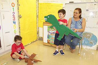 Niño y niña preparan animales de cartón en el salón